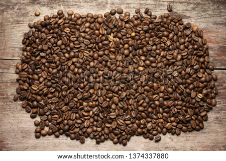 Pile of roasted coffee beans on old wooden background. Top view point. #1374337880