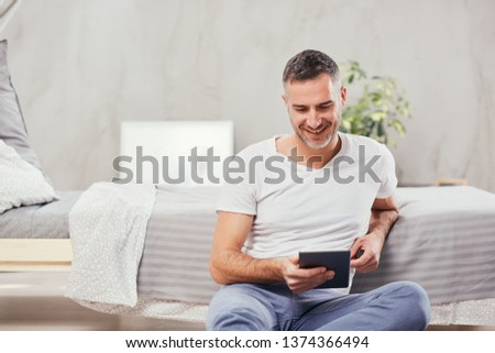 Handsome Caucasian middle-aged man sitting on the floor in bedroom and leaning on bed. In holding hands tablet. #1374366494