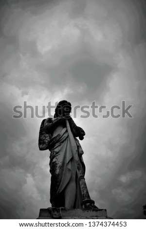 Stone figure of an angel with a dark sky above her.  #1374374453