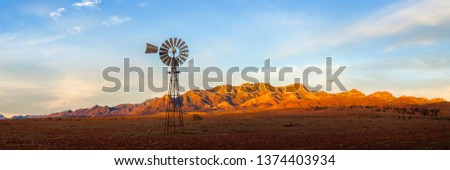 A windmill with the Flinders Ranges behind it in the Australian outback. Flinders Ranges National Park, South Australia, Australia. #1374403934