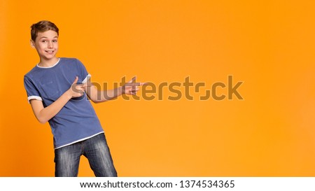 Great promo. Cheerful teen boy pointing two fingers aside at free space, orange panorama background