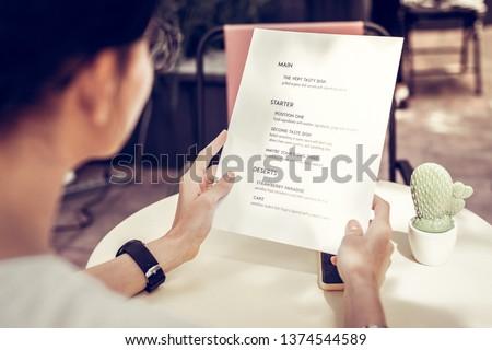 Restaurant menu. Close up of a restaurant menu being in female hands #1374544589