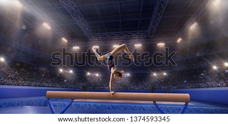 Female athlete doing a complicated exciting trick on gymnastics balance beam in a professional gym. Girl perform stunt in bright sports clothes #1374593345