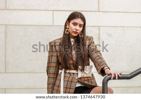 Portrait shooting of a stylish girl. Beige shades. Trends of spring and summer 2019. Bike shorts. Thick cloak, cover jacket. Gold earrings. Heels #1374647930