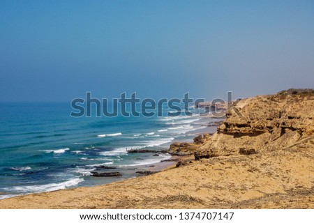 a view from the top of a mountain overlooking the beach and the atlantic sea outside of oualidia, morocco, with a bright sun and sparsely clouded skies #1374707147