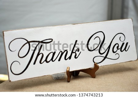 Wedding decorations Rustic theme event with a Thank you sign on the sign in table at the wedding Reception. The wedding guest sign in book goes on the table as well as party favors for guest.