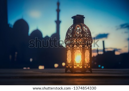 Ramadan Kareem greeting photo with serene mosque background with beautiful glowing lantern.  #1374854330