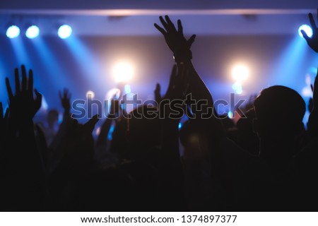 Blurred photo of Christian worship God together in Church ,raised hand and praise the LORD ,concert background. #1374897377