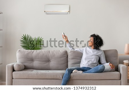 Smiling young African American woman using air conditioner, cooler system remote controller, switching, setting comfort temperature in living room, resting on cozy sofa at home, enjoy fresh air #1374932312