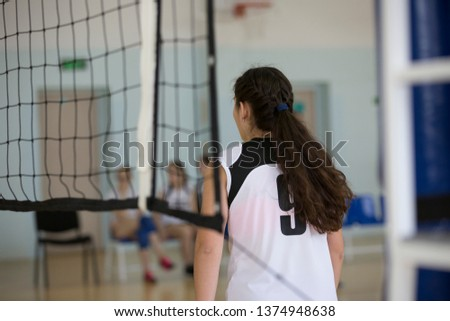 Volleyball girl stands at the volleyball net. In the background are spare players. #1374948638
