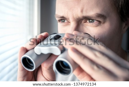 Man with binoculars. Private detective, agent or investigator looking out the window. Man spying or investigating. Privacy, surveillance or espionage concept. Suspicious or curious person spying. #1374972134