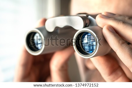 Man watching out the window with binoculars. Curious and nosy neighbour. Private detective or undercover cop investigating or spying. Curious person or stalker. #1374972152