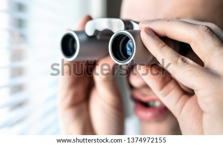 Nosy neighbor or stalker with binoculars. Funny crazy man staring at people. Curious guy looking out the window. Silly face. Snooping and searching rumour or gossip. Peeping tom, pervert or voyeur. #1374972155