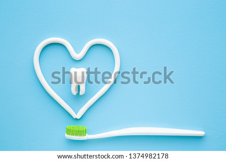 Toothbrush with green bristles on pastel blue background. Heart shape created from paste. White tooth in middle of heart. Love healthy teeth. Empty place for text, quote, sayings or logo. Closeup. #1374982178