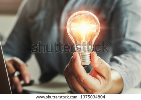 hand holding light bulb. idea concept with innovation and inspiration #1375034804