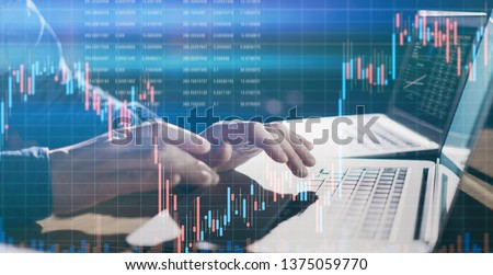Analyst using laptop and researching the financial data at his office. Concept of a digital diagram, graph interface, virtual screen, technical price indicator, trading online, global market Royalty-Free Stock Photo #1375059770