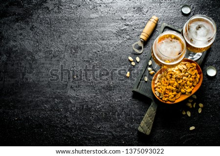Two glasses of beer and peanuts in a bowl on a black cutting Board. On black rustic background #1375093022