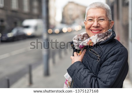 Portrait of beautiful senior woman with a jacket on a windy day in an urban city environment, happy and cheerful #1375127168