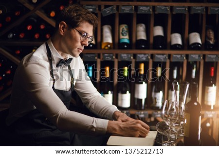 Wine degustator man taking notes in winery with wine bottles stacked in rows on the shelves. Bartender writing in notepad information of wine origin and taste. #1375212713