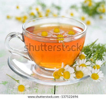 Chamomile tea in a glass cup on a white table #137522696