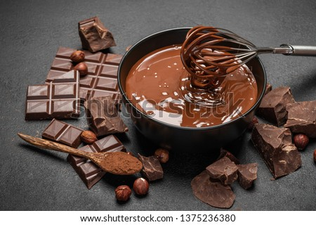 ceramic bowl of chocolate cream or melted chocolate and pieces of chocolate on dark concrete background #1375236380