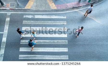 Top aerial view crosswalk with people walk across road with signage. Concept Pedestrians passing a crosswalk. Rush hour in the city #1375245266