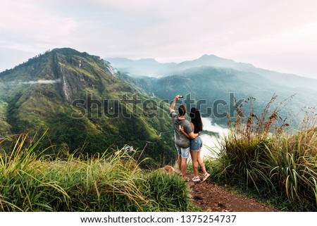 A couple in love takes a selfie. Man and woman holding hands. The couple travels around Asia. Travel to Sri Lanka. Honeymoon trip. Wedding travel. Tourists in the mountains. Dawn in the mountains