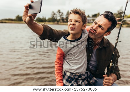 Close up of father and son taking a selfie while fishing near a lake. Happy father and son making faces while takes a selfie near the lake holding a fishing rod. #1375273085
