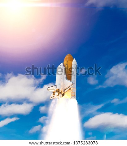 Dramatic launch. Rocket launching. Blue sky. CLouds and sun flare. Elements of this image furnished by NASA. #1375283078