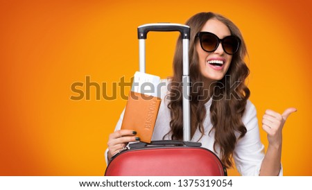 Weekends getaway. Girl with tickets and suitcase showing thumb up, orange background #1375319054