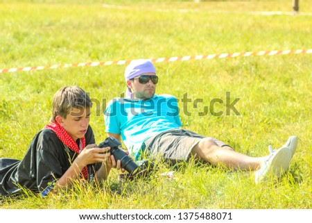 RUSSIA, YAROSLAVL - 30 JUN 2012: serious guy photographer with a camera in his hands in summer forest tent camp play active games on banks Volga river participate in competitions on bright Sunny day #1375488071