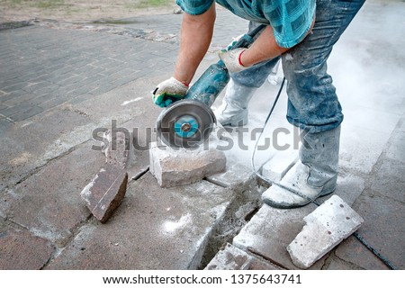 Worker saws  stone with circular saw for repairing and renewal the walkway. Builder, work on laying paving slabs. Tiler cuts paving slab using electric cut-off saw #1375643741