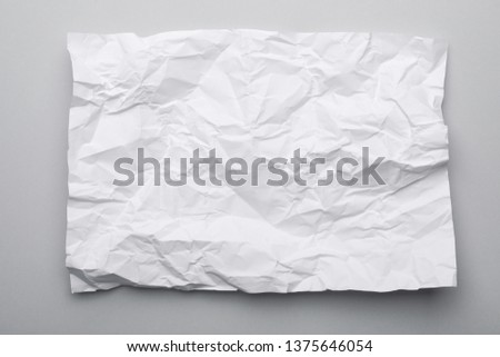 Sheet of crumpled paper on grey background, top view Royalty-Free Stock Photo #1375646054