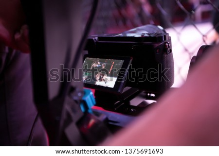 Video filming in the backstage of a sporting event. Athletes fighters in oktogon in front of the camera after the fight. Operator with a professional video camera during the event, rear view #1375691693