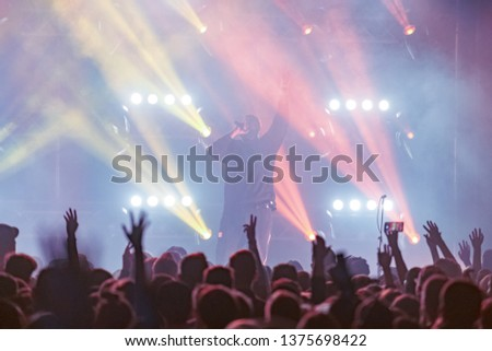 concert, silhouettes of happy people raising up hands, Music show. Bright scene lighting in club. Fans burn red flares at hip hop #1375698422