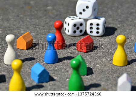Differently colored game figures stand together with cubes and small houses in different colors on a stone basis and cast by the high sun a shadow #1375724360