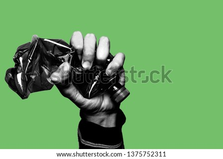 Concept of stop plastic pollution, global warming, recycling plastic, plastic free. Hand tightly squeezes an empty plastic bottle in a sign of protest in black and white. Green background. Copy space Royalty-Free Stock Photo #1375752311