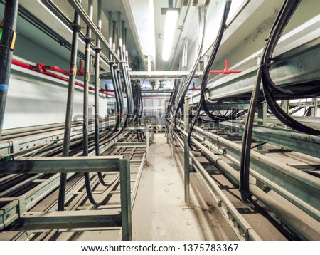 Power cables and instrument cables were installed with cable trays in electric cable room of power plant which show metal material of tray and black high voltage cable. #1375783367