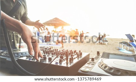 Dj mixing at sunset beach party in summer vacation outdoor - Disc jockey hands playing music for tourist people in chiringuito kiosk bar - Event, music and fun concept - Focus on right hand  #1375789469
