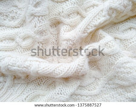 Knitted clothes from wool yarn. Background of wool yarn for yarn frame. White knitting yarn for handicrafts background. #1375887527