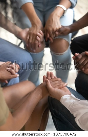 Close up vertical view diverse people sitting on chairs in circle hold hands, drug alcohol addiction rehab, support group counseling, therapy session, religious team, psychological help trust concept #1375900472