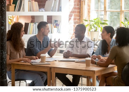 Diverse employees listen group leader people gathered in boardroom working discuss project morning briefing, positive students study together sitting at office table library or classroom concept image