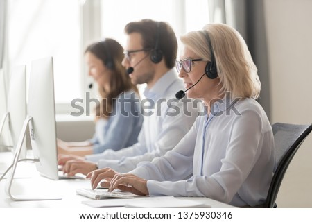 Call center workers working use headset look at computer screen, focus on blond aged female employee receive record and relay messages from customers, provide assistance and support distantly concept #1375930346