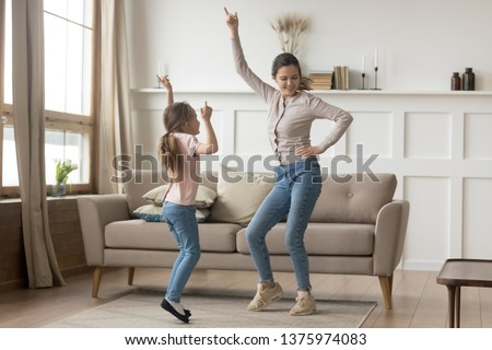Active family young mother dance having fun with little preschool or school age daughter older younger sister listens happy song moving together, leisure activities with kid positive emotions concept #1375974083