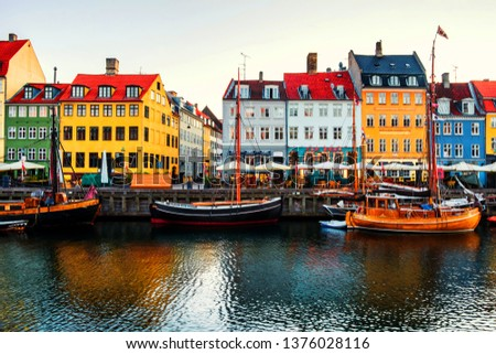 Copenhagen, Denmark. View of famous Nyhavn area in the center of Copenhagen, Denmark in the morning. Boats moored with historical buildings, clear bright sky #1376028116