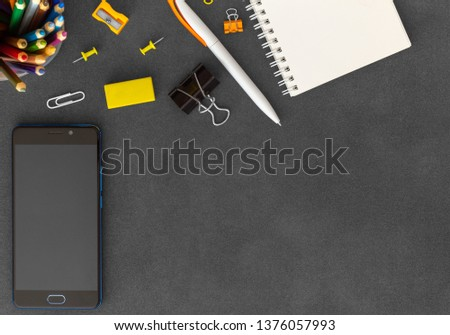 Mobile phone with blank white spiral paper notebook, pen, paper clumps, paper clips, eraser, push pins, sharpener and colored pencils on empty dark background top view #1376057993