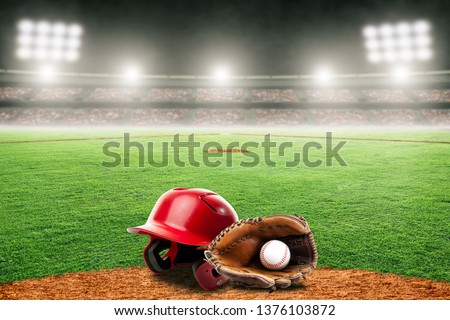 Baseball helmet, glove and ball on field at brightly lit outdoor stadium. Focus on foreground and shallow depth of field on background and copy space. Royalty-Free Stock Photo #1376103872