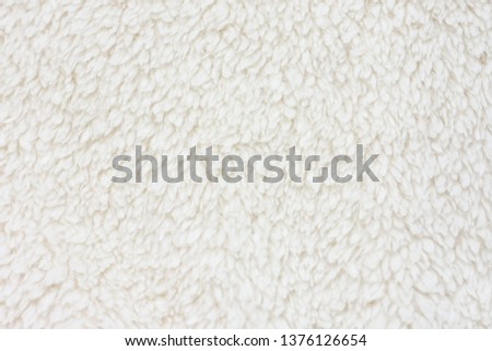Background picture of a soft fur white carpet. wool sheep fleece closeup texture background. Fake color beige fur fabric. top view.  #1376126654