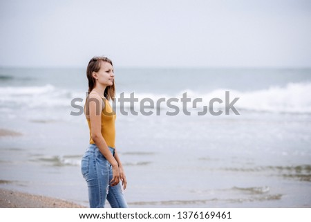 Young beautiful girl walking on the beach on a cloudy morning. She watches as the waves approach the shore.  #1376169461
