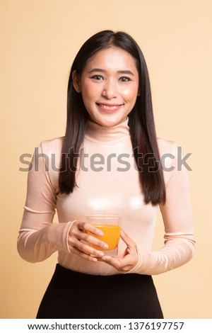 Young Asian woman drink orange juice on  beige background #1376197757